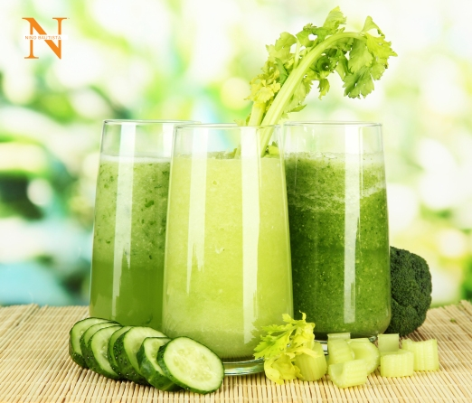 Glasses of green vegetable juice on bamboo mat, on green background